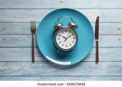 Meal planning for diet concept , Intermittent fasting concept with clock on plate, fork and knife on wooden table, Clock on plate with fork and knife, intermittent fasting, meal plan, weight loss