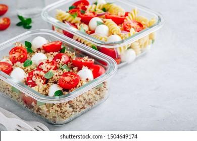 Conteneurs de préparation de repas avec salade de pâtes ou quinoa, tomates, fromage mozzarella et basilic. Vue de dessus, espace de copie