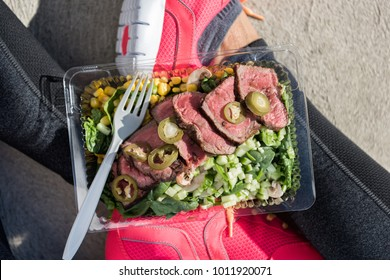 Meal prep fitness lifestyle - Woman taking food selfie top view photo of her prepared ready to go lunch box for healthy paleo diet - Steak salad take-out eating girl at gym.