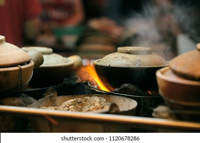 Meal preparation using clay pot on charcoal fire.