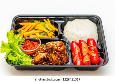 Meal set with rice, grilled chicken, sausage, carrot and cucumber dish and chili sauce