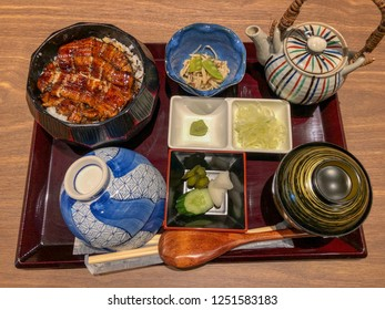 Meal set of Unagi donburi's a bowl filled with steamed white rice,topped with fillets of eel (unagi),glazed with a sweetened soy based sauce, called tare and caramelized,with Japanese side dish.