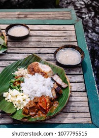 Meal set of various traditional Filippino Food,  Pakbet on banana leaves and wooden table, top view