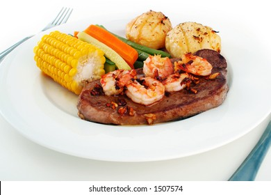 Meal setting of a steak with garlic butter sauce and fresh king prawns - surf n' turf - and fresh vegetables, on a white plate with knife and fork isolated on white