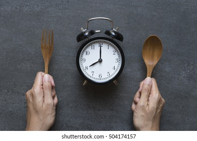 Meal time with alarm clock, hand holding spoon and fork