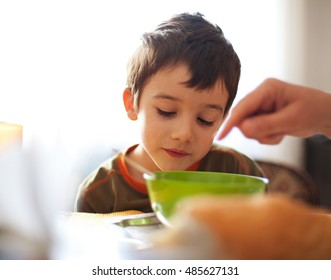 Meal time for a child, hand pointing the plate