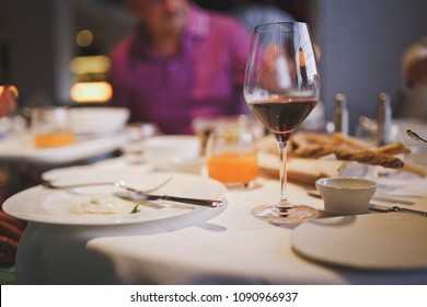 Meals are served at the restaurant. On the table there is red wine in the glass, cutlery and plates in the process of eating. Life style.
