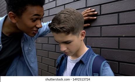 Mean african american student mocking weak boy, psychological abuse, threat