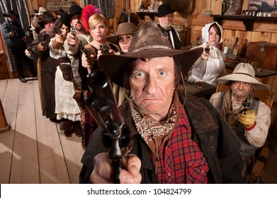 Mean gunfighter with pistol aimed in old saloon