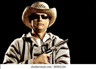 Mean looking man holding handgun with Mexican style clothes.