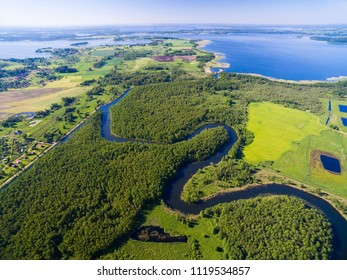 Meander of Wegorapa river flowing across wetlands, Mazury, Poland. Mamry Lake in the background