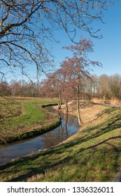 Meandering brook in winter landscape in the Netherlands