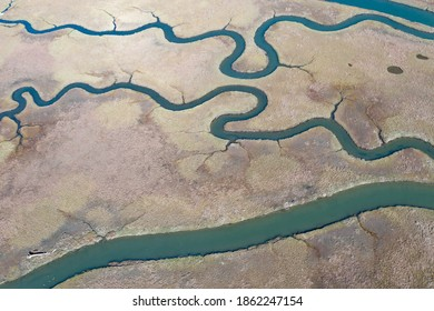 Meandering channels run through a beautiful estuary in Central California. Estuaries form when freshwater runoff meets and mixes with saltwater from the ocean. Lots of wildlife rely on estuaries.