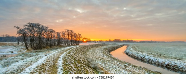 Meandering River in Frozen grassland landscape on early morning with rising sun under beautiful sky