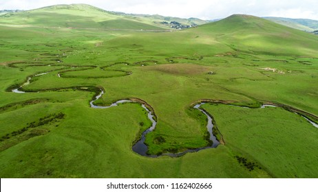 Meandering stream with mountains and clouds at The Persembe Plateau at Ordu, Turkey