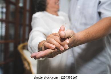 Meaningful moments. Lover senior couple dance together at home. Happy Anniversary cute family. Selective focus at hand.