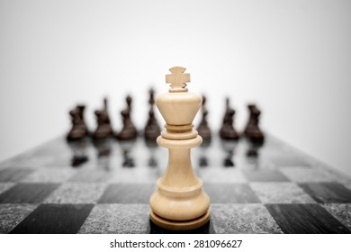 The meaningful photo of chess king staying before the set of another colour pieces.