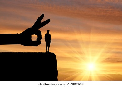 Meanness and treachery concept. Silhouette hand wants to push a man off a cliff