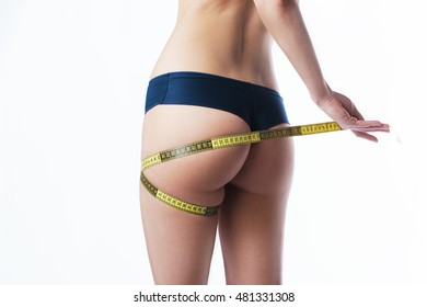 Measure on woman body on white background. Fashion photo of sexy young woman in lingerie with slim body sitting on a diet and measuring the waist with a centimeter tape