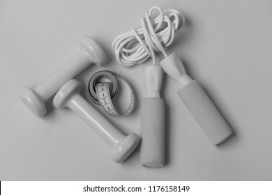 Measure tape, dumbbells and skipping rope in cyan color on blue background. Fit shape and sport concept. Jump rope, tape roll and barbells placed next to each other. Health regime and fitness symbols.