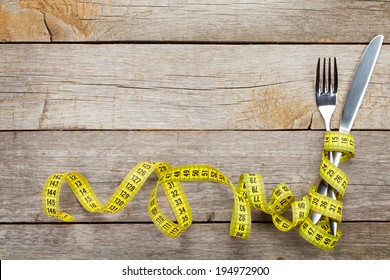 Measure tape with knife and fork. Diet food on wooden table with copy space