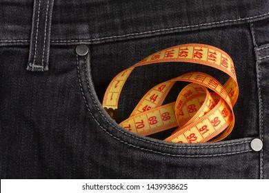 Measure tape lies in black jeans.