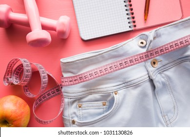 Measure tape with light blue jeans, dumbbells, apple, notebook on the pastel pink background. Women diet before summer season. Healthy lifestyle, body slimming, weight loss concept. Cares about body.