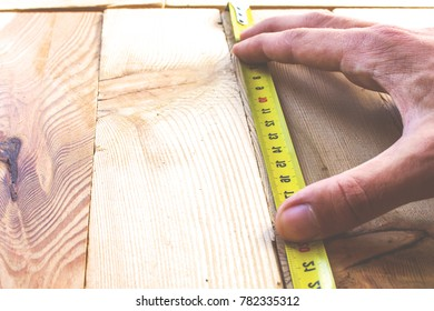 Measure with a tape measure on a wooden board, retro toned
