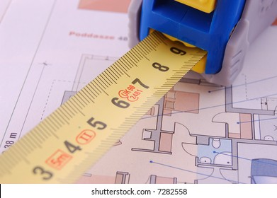 Measure tape over construction plan