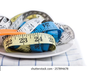 Measure tape ,white ,yellow ,and blue on white plate with white background