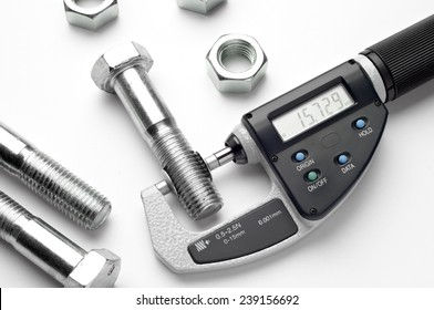 Measurement of details in the bolts and nuts industry. Measuring a diameter of a bolt with digital micrometer