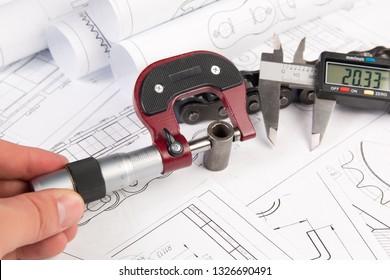 Measurement of metal part with micrometer on engineering drawings