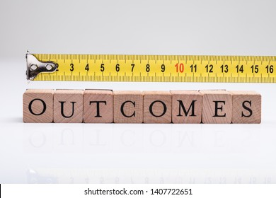 Measurement Of Outcomes Word On Wooden Blocks Using Measuring Tape