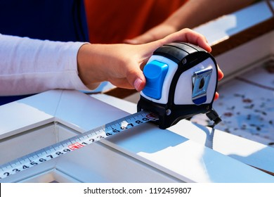 Measurement of the size of a frame of a window tape measure. Concept exact calculation, wise decision. Close-up A tape measure in a hand