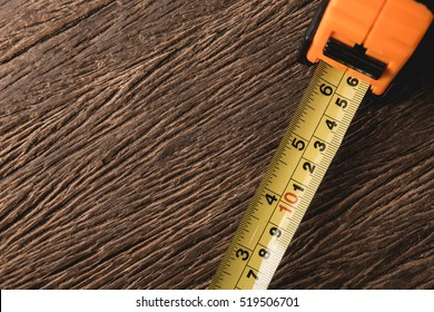 Measurement tape on grunge wood background