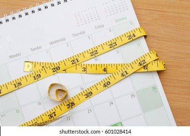 Measurement tape is twisted around the calendar. Weight management concept.