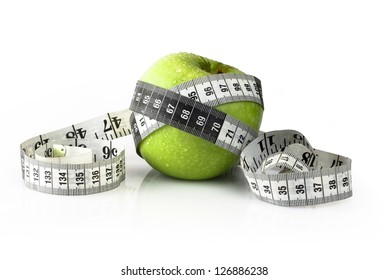 Measurement tape wrapped around a green apple