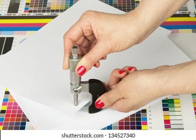 Messung der Dicke eines Papierblattes durch einen Mikrometer in der Druckerei