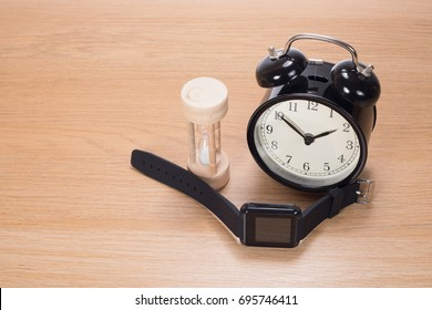 Measurement of time concept with a small egg timer, wristwatch and alarm clock on a wooden table with copy space viewed high angle