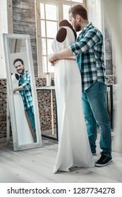 Measurement of waistline. Bearded male designer making measurement of waistline for long white dress