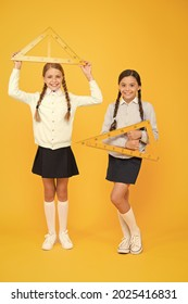 Measuring angles at geometry. Cute schoolgirls holding triangles for geometry lesson on yellow background. Little girls learning geometry. Small children with geometrical tools for geometry