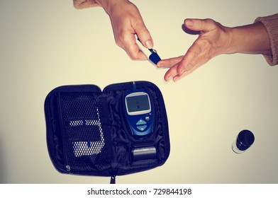 Measuring blood sugar with a glucometer at home. Scarification - the taking of capillary blood from the finger. An elderly woman pierces a finger on a white background. pancreatic diabetes