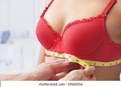 Measuring bust base size of woman wearing red bra