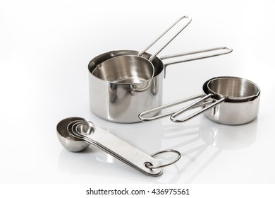 Measuring cups and spoons on white background