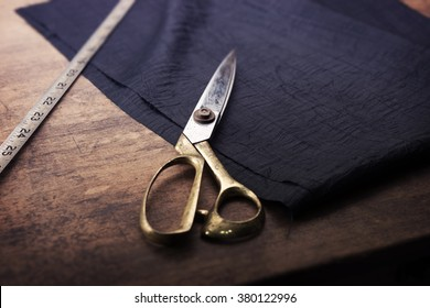 Measuring and cutting textile or fine cloth. Work table of a tailor. Gold scissors and black silky fabric. Intentionally shot in retro muted color.