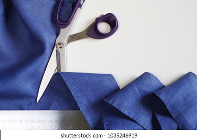 Measuring and cutting textile. Scissors and violet linen fabric. Copy space