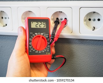 Measuring electricity in a socket using a multimeter in the hand. Red pocket digital multimeter with LCD display. Test leads in the socket. High-quality Close-up photography.