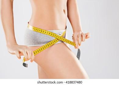 Measuring girl's waist wearing gray underwear at gray studio background, copy space.