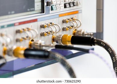 Measuring high-frequency equipment. High-frequency connectors are inserted in the instrument panel. Abstract industrial background.
