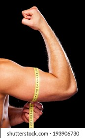 Measuring his perfect bicep. Close-up of muscular man measuring his bicep with measuring tape while standing against grey background